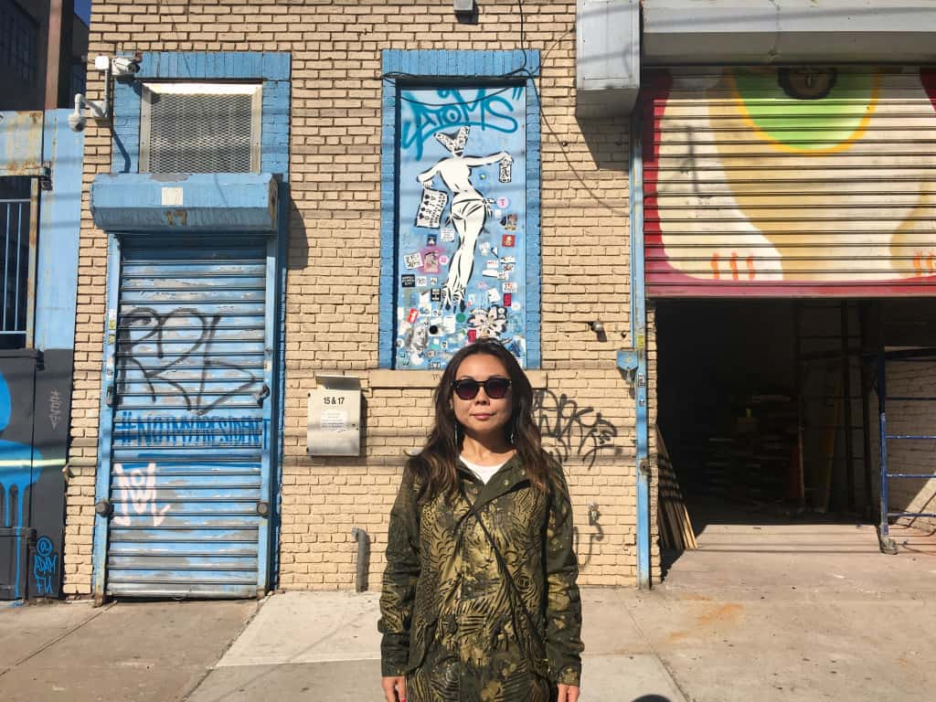 Lady Aiko, standing in front of her stencil piece in Brooklyn
